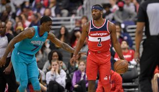 Washington Wizards guard John Wall (2) dribbles the ball against Charlotte Hornets forward Dwayne Bacon (7) during the first half of an NBA basketball game, Saturday, March 31, 2018, in Washington. (AP Photo/Nick Wass)