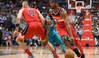 Washington Wizards guard John Wall (2) dribbles the ball during the second half of an NBA basketball game against the Charlotte Hornets, Saturday, March 31, 2018, in Washington. The Wizards won 107-93. (AP Photo/Nick Wass)