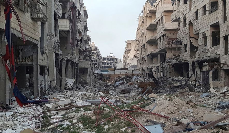 This Monday, March 26, 2018, file photo provided by Danny Makki, a British-born Syrian journalist, which has been verified and is consistent with other AP reporting, shows a view of damaged buildings due to fighting and Syrian government airstrikes in the town of Harasta, in eastern Ghouta region east of Damascus, Syria. The Syrian army declared victory in eastern Ghouta Saturday, March 31, 2018, after opposition fighters evacuated from most of the area near the capital except for the town of Douma where negotiations are still underway for rebels there to leave or face an all-out government offensive. (Danny Makki via AP) ** FILE **