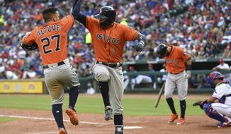 Houston Astros' Jose Altuve (27) and Carlos Correa (1) celebrate Correa's home run with scored Altuve in the seventh inning of a baseball game, Saturday, March 31, 2018, in Arlington, Texas. (AP Photo/Jeffrey McWhorter)