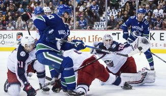 Columbus Blue Jackets goalie Joonas Korpisalo (70), of Finland, stops Vancouver Canucks' Bo Horvat (33) as Daniel Sedin (22), of Sweden, looks on during the second period of an NHL hockey game in Vancouver, British Columbia, Saturday March 31, 2018. (Darryl Dyck/The Canadian Press via AP)