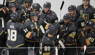 Vegas Golden Knights players celebrate after defeating the St. Louis Blues in overtime of an NHL hockey game, Friday, March 30, 2018, in Las Vegas. (AP Photo/John Locher)
