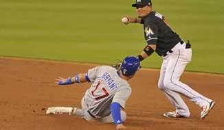 Miami Marlins' Miguel Rojas, right, tags out Cub's Kris Bryant, left, in the third inning of a baseball game in Miami, Saturday, March 31, 2018. (AP Photo/Gaston De Cardenas)