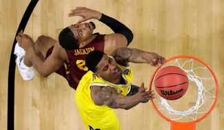 Michigan guard Charles Matthews dunks the ball ahead of Loyola-Chicago forward Aundre Jackson, left, during the first half in the semifinals of the Final Four NCAA college basketball tournament, Saturday, March 31, 2018, in San Antonio. (AP Photo/Eric Gay)