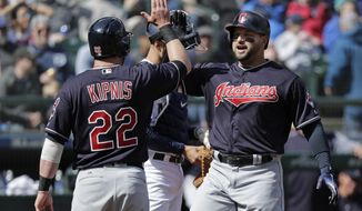 Cleveland Indians' Yonder Alonso, right, is greeted at the plate by Jason Kipnis (22) after hitting a grand slam during the first inning of a baseball game against the Seattle Mariners, Saturday, March 31, 2018, in Seattle. (AP Photo/Ted S. Warren)