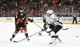 Anaheim Ducks' Rickard Rakell, left, of Sweden, shoots to score an overtime winner under pressure by Los Angeles Kings' Alec Martinez in overtime an NHL hockey game Friday, March 30, 2018, in Anaheim, Calif. The Ducks won 2-1. (AP Photo/Jae C. Hong)
