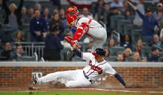 Atlanta Braves Ryan Flaherty slides under Philadelphia Phillies catcher Andrew Knapp (15) to score in the third inning of a baseball game, Friday, March 30, 2018, in Atlanta. (AP Photo/Todd Kirkland)