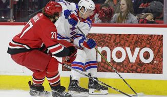 Carolina Hurricanes' Justin Faulk (27) defends while New York Rangers' Filip Chytil, of the Czech Republic, skates during the first period of an NHL hockey game in Raleigh, N.C., Saturday, March 31, 2018. (AP Photo/Gerry Broome)