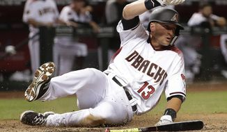 Arizona Diamondbacks Nick Ahmed scores on a base hit by David Peralta against the Colorado Rockies during the sixth inning of a baseball game Thursday, March 29, 2018, in Phoenix. (AP Photo/Matt York)