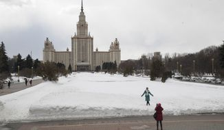 In this Wednesday, March 28, 2018 photo, a tourist takes a picture in the area where the fan zone of the Russia Soccer World Cup 2018 will be placed, with Moscow State University main building in the background in Moscow, Russia.  At Moscow State University, Russia's oldest and most prestigious, there will be a 25,000-capacity fan zone outside the main building during exam season, prompting thousands of students to campaign against the tournament. (AP Photo/Pavel Golovkin)
