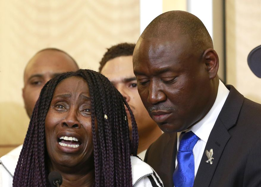 FILE - In this Monday March 26, 2018, file photo, attorney Benjamin Crump, right, stands alongside Sequita Thompson as she breaks into tears while talking about the fatal police shooting of her grandson Stephon Clark during a news conference, in Sacramento, Calif. Over the years, Crump has represented the relatives of other unarmed black men fatally shot by police in other parts of the country. (AP Photo/Rich Pedroncelli, File)