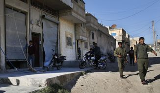 Members of the Kurdish internal security forces, right, pass next of damaged shops, at the scene where an explosion on Thursday hit a U.S.-led coalition vehicles, killing an American and a Briton soldiers, in Manbij town, north Syria, Saturday, March 31, 2018. The explosion on Thursday was the first to hit members of the U.S.-led coalition who have deployed to Manbij months after the town was liberated from Islamic State militants in 2016. An improvised explosive device went off during an operation against a known member of the Islamic State group in this mixed Arab and Kurdish town, the U.S-led Coalition said in a statement Saturday. (AP Photo/Hussein Malla)