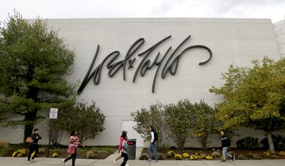 People walk on a sidewalk along the entrance to Lord & Taylor department store at Garden State Plaza, Wednesday, Oct. 25, 2017, in Paramus, N.J. (AP Photo/Julio Cortez)