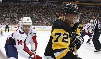 Pittsburgh Penguins' Patric Hornqvist (72) digs the puck out of the corner with Washington Capitals' John Carlson (74) defending during the second period of an NHL hockey game in Pittsburgh, Sunday, April 1, 2018. (AP Photo/Gene J. Puskar) ** FILE **