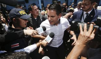 Presidential candidate Fabricio Alvarado, with the National Restoration party, talks to the press after he cast his vote at a polling station during general elections in San Jose, Costa Rica, Sunday, April 1, 2018. Voters will choose between Carlos Alvarado of the ruling Citizen Action Party and Fabricio Alvarado of National Restoration Party in a second-round runoff. (AP Photo/Arnulfo Franco)