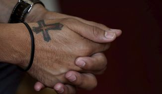 A Christian man sports a tattoo of religious cross on his hand during an Easter mass at Saint Marks Cathedral church in Bangalore, India, Sunday, April 1, 2018. (AP Photo/Aijaz Rahi)