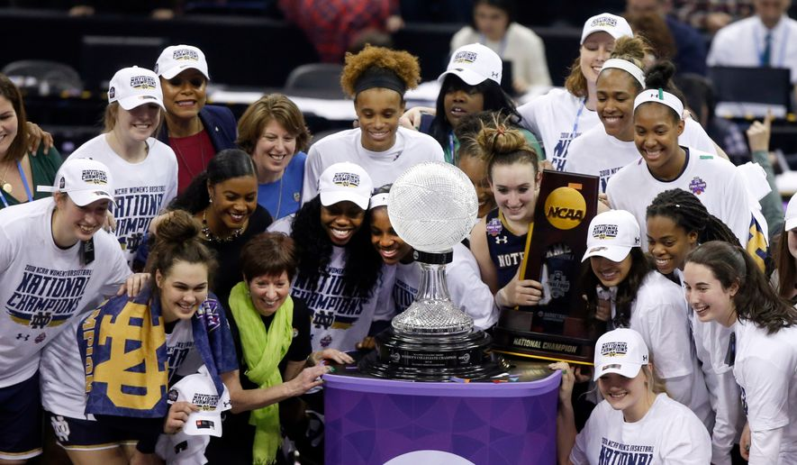 Members of Notre Dame celebrate with the trophy after defeating Mississippi State in the final of the women's NCAA Final Four college basketball tournament, Sunday, April 1, 2018, in Columbus, Ohio. Notre Dame won 61-58. (AP Photo/Ron Schwane)