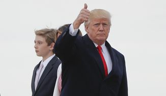President Donald Trump, center, gives a thumbs-up from the tarmac upon his arrival with first lady Melania Trump and their son Barron at Andrews Air Force Base, Md., Sunday, April 1, 2018. Trump returned to Washington after spending Easter weekend at his Mar-a-Lago estate. (AP Photo/Pablo Martinez Monsivais)