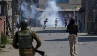Kashmiri protesters engulfed in tear gas smoke clash with Indian paramilitary soldiers during a protest against the killing of rebels in Srinagar, Indian controlled Kashmir, Sunday, April 1, 2018. At least eight rebels have been killed in fighting with Indian troops in disputed Kashmir, triggering a new round of anti-India protests and clashes, officials said Sunday.(AP Photo/Dar Yasin)