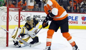 Philadelphia Flyers' Claude Giroux, right, scores past Boston Bruins goalie Anton Khudobin during overtime to win an NHL hockey game Sunday, April 1, 2018 in Philadelphia. The Flyers won 4-3. (AP Photo/Tom Mihalek)