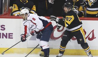 Pittsburgh Penguins' Sidney Crosby (87) and Washington Capitals' Alex Ovechkin (8) work along the boards during the first period of an NHL hockey game in Pittsburgh, Sunday, April 1, 2018. (AP Photo/Gene J. Puskar) ** FILE **