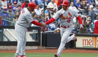 St. Louis Cardinals third base coach Jose Oquendo, left, congratulates the Cardinals' Paul DeJong (12) who hit a solo home run during the second inning of a baseball game against the New York Mets, Sunday, April 1, 2018, in New York. (AP Photo/Kathy Willens)