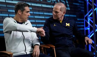 """Villanova head coach Jay Wright, left, and Michigan head coach John Beilein shake hands during an interview for CBS Sports Network's """"We Need to Talk"""" show before the championship game of the Final Four NCAA college basketball tournament, Sunday, April 1, 2018, in San Antonio. (AP Photo/David J. Phillip)"""