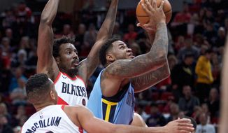 Memphis Grizzlies forward Jarell Martin, right, shoots in front of Portland Trail Blazers forward Al-Farouq Aminu, left rearl during the first half of an NBA basketball game in Portland, Ore., Sunday, April 1, 2018. (AP Photo/Craig Mitchelldyer)