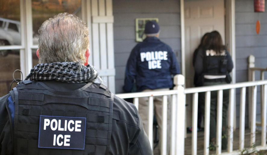 In this Feb. 9, 2017, photo provided by U.S. Immigration and Customs Enforcement, ICE agents stand outside a home in Atlanta during a targeted enforcement operation aimed at immigration fugitives, re-entrants and at-large criminals living in the country illegally. (Bryan Cox/ICE via AP) **FILE**
