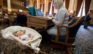 In this Feb. 20, 2018, photo, Rep. Megan Jones has her daughter, Alma Jones, at her House seat in the Iowa Statehouse in Des Moines, Iowa. Jones closed a chapter in her work life of regularly bringing along her newborn baby to the state Capitol. She started bringing her daughter, Alma, to the statehouse just a few weeks after giving birth on Jan. 24. Jones announced that Alma is now headed to her next adventure: day care. (Rodney White/The Des Moines Register via AP)