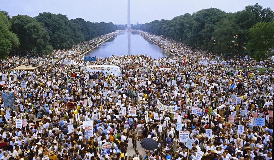 FILE - In this June 19, 1968 file photo, demonstrators march on Washington during the Poor Peoples' Campaign Solidarity Day. From the civil rights protests of the 1960s to the marriage equality movement, civil disobedience has taken on different forms in the years since Martin Luther King, Jr. was assassinated. (AP Photo/Charles Tasnadi, File)