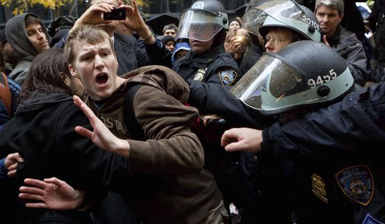 FILE - In this Thursday, Nov. 17, 2011 file photo, an Occupy Wall Street protestor is grabbed by police as he tries to escape a scuffle in Zuccotti Park in New York. (AP Photo/John Minchillo)