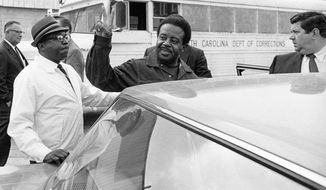 FILE - In this May 2, 1969 file photo, Rev. Ralph David Abernathy gives the victory sign as he is escorted back to jail from Charleston County Court in Charleston, S.C., wear he and others were taken for hearings on violating an injunction limiting pickets at two hospitals. The members of King's tight circle barely paused to grieve, after Martin Luther King Jr. was assassinated. They plunged into carrying out his unfinished work and turned it into a lifelong vow. (AP Photo/Lou Krasky, File)