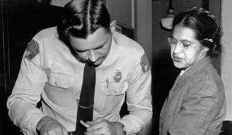 In this Feb. 22, 1956, file photo, Rosa Parks is fingerprinted by police Lt. D.H. Lackey in Montgomery, Ala., two months after refusing to give up her seat on a bus for a white passenger on Dec. 1, 1955. On May 29, 2019, Gov. Kay Ivey signed legislation creating a Women's Tribute Statue Commission to fund, commission and place a statue of Parks on Alabama State Capitol grounds. (AP Photo/Gene Herrick, File) **FILE**