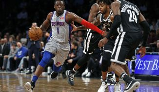 Detroit Pistons guard Reggie Jackson (1) drives to the basket past Brooklyn Nets guard D'Angelo Russell (1) and Nets forward Rondae Hollis-Jefferson (24) during the first half of an NBA basketball game Sunday, April 1, 2018, in New York. (AP Photo/Adam Hunger)