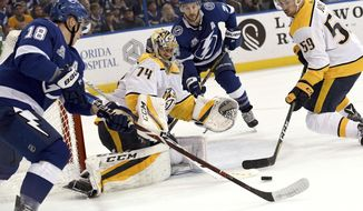 Nashville Predators goaltender Juuse Saros (74) knocks the puck away as Tampa Bay Lightning left wing Ondrej Palat (18) looks for a shot during the second period of an NHL hockey game Sunday, April 1, 2018, in Tampa, Fla. (AP Photo/Jason Behnken)