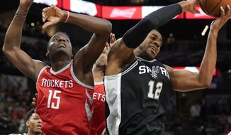 San Antonio Spurs' LaMarcus Aldridge (12) grabs the rebound away from Houston Rockets' Clint Capela during the first half of an NBA basketball game, Sunday, April 1, 2018, in San Antonio. (AP Photo/Darren Abate)