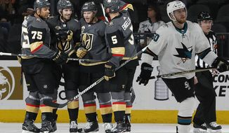 Vegas Golden Knights celebrate after center Oscar Lindberg, third from left, scored against the San Jose Sharks during the second period of an NHL hockey game, Saturday, March 31, 2018, in Las Vegas. (AP Photo/John Locher)