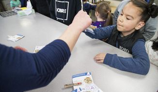 """Kindergartener Jasmin Hernandez receives a prize and her """"clip-up"""" pin after being called to the office during morning announcements at McKinley Elementary School in Yakima, Wash., Tuesday, March 20, 2018. The program is part of the schools efforts to address behavior issues in students who have experienced trauma. (Shawn Gust/Yakima Herald-Republic via AP)"""