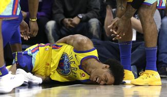 Golden State Warriors guard Patrick McCaw lays on the court in pain after falling hard to the floor late in the third quarter following a Flagrant 1 foul by Sacramento Kings's Vince Carter in an NBA basketball game Saturday, March 31, 2018, in Sacramento, Calif. McCaw was taken off the court on a stretcher. The Warriors won 112-96. (AP Photo/Rich Pedroncelli)