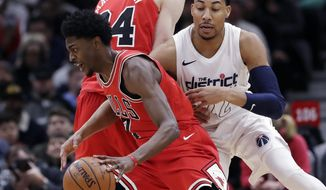 Chicago Bulls guard Justin Holiday, left, drives to the basket as Washington Wizards forward Otto Porter Jr., guards during the first half of an NBA basketball game Sunday, April 1, 2018, in Chicago. (AP Photo/Nam Y. Huh)