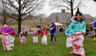 Isabella Deng, 8, (right) out-hops her sister Oceana Deng, 6, (behind) in a sack race at the Smithsonian Zoo on April 2nd, 2018, while in town with her New York City family for Easter. The Deng family is part of a growing group of tourists and DMV residents joining the African America tradition of Easter Monday at the zoo. (Photos by Julia Airey / The Washington Times)