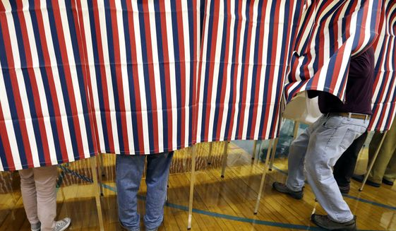 In this Nov. 8, 2016, file photo, a voter enters a booth at a polling place in Exeter, N.H. (AP Photo/Elise Amendola, File)
