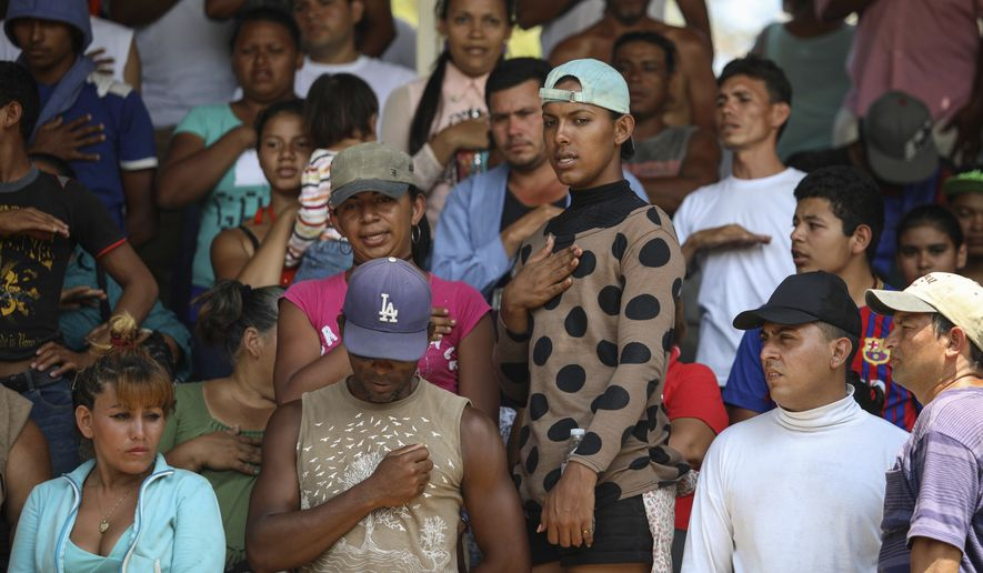 "Central American migrants from Honduras sing their national anthem during the annual Migrant Stations of the Cross caravan or ""Via crucis,"" organized by the ""Pueblo Sin Fronteras"" activist group, as the group makes a few-days stop in Matias Romero, Oaxaca state, Mexico, Monday, April 2, 2018. While a group of about a couple of hundred men in the march broke off and hopped a freight train north on Sunday, the rest seem unlikely to move until Wednesday or Thursday, and are probably going to take buses to the last scheduled stop for the caravan, a migrant rights symposium in central Puebla state. (AP Photo/Felix Marquez)"