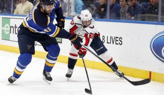 St. Louis Blues' Robert Bortuzzo (41) and Washington Capitals' Shane Gersich (63) chase after a loose puck along the boards during the first period of an NHL hockey game Monday, April 2, 2018, in St. Louis. (AP Photo/Jeff Roberson)