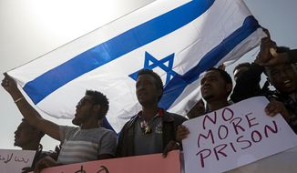 In this Feb. 22, 2018, file photo, asylum seekers march during a protest outside Israeli Prison Saharonim, in the Negev desert, southern Israel. (AP Photo/Tsafrir Abayov, File)