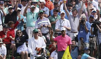 The massive gallery following Tiger Woods reacts as he chips in for an eagle on the second hole during practice for the Masters golf tournament at Augusta National Golf Club, Monday, April 2, 2018, in Augusta, Ga.  (Curtis Compton/Atlanta Journal-Constitution via AP)