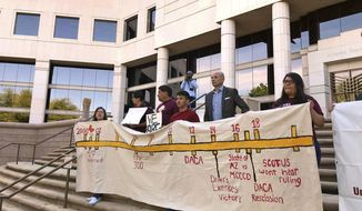 In this photo taken outside the Arizona State Supreme Court in Phoenix, Monday, April 2, 2018, immigrant students with deferred deportation status hold a banner in support asking the Supreme Court to rule in favor of continuing their access to in-state tuition costs. The Court said Monday that before colleges send out tuition letters for the next semester it will rule on whether immigrant students with deferred deportation status can continue to benefit from lower in-state school costs. (AP Photo/Anita Snow)