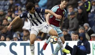 West Bromwich Albion's Ahmed Hegazi, left, and Burnley's Ashley Barnes during the English Premier League soccer match at The Hawthorns in West Bromwich, England, Saturday March 31, 2018. (David Davies/PA via AP)