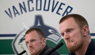 Vancouver Canucks Henrik, right, and Daniel Sedin announce their retirements from hockey during a news conference at Rogers Arena in Vancouver, Monday, April, 2, 2018. (Jonathan Hayward/The Canadian Press via AP)